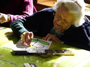 Fotografía en la que se puede ver una anciana pintando en nuestros talleres