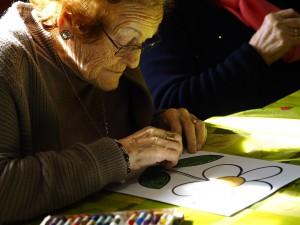 Fotografía en la que se puede ver una anciana pintando una flor