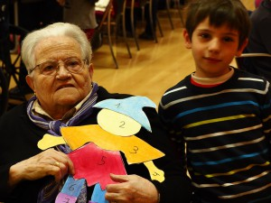 Fotografía en la que se pueden ver a un niño y una anciana participando en nuestros programas especiales