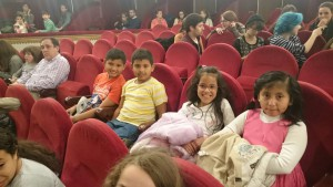 Fotografía en la que se puede ver unos niños disfrutando de actividades culturales en un teatro