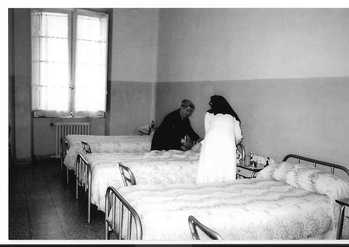 Hermana con asiliado haciendo las camas ASVAI